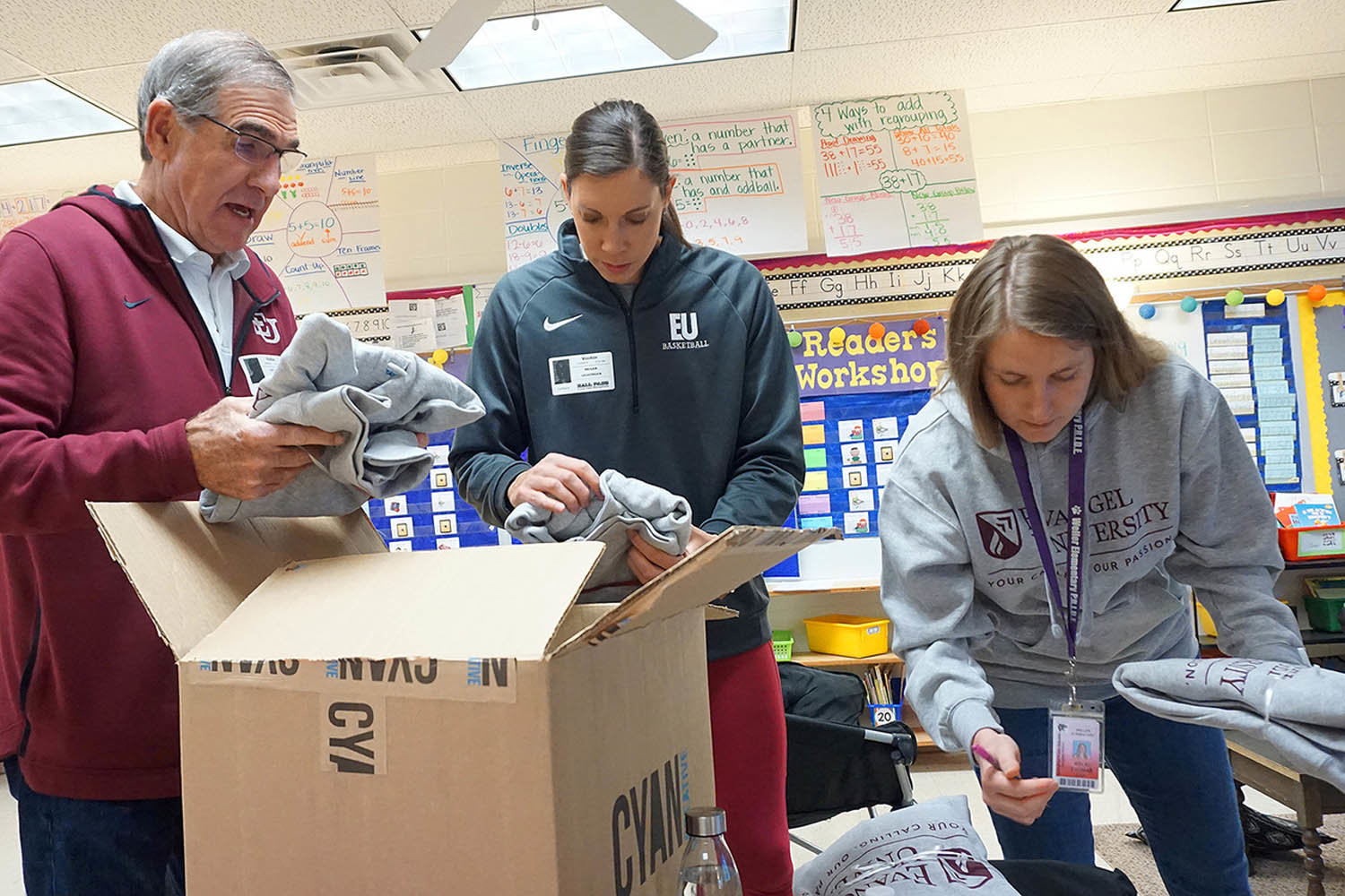 LUNCH MONEYEvangel athletes donated sweatshirt hoodies to all 367 students, teachers and staff at Weller Elementary School. Above, basketball coaches Steve Jenkins and Meghan Leuzinger sort hoodies in Kelsi Thomas' class.