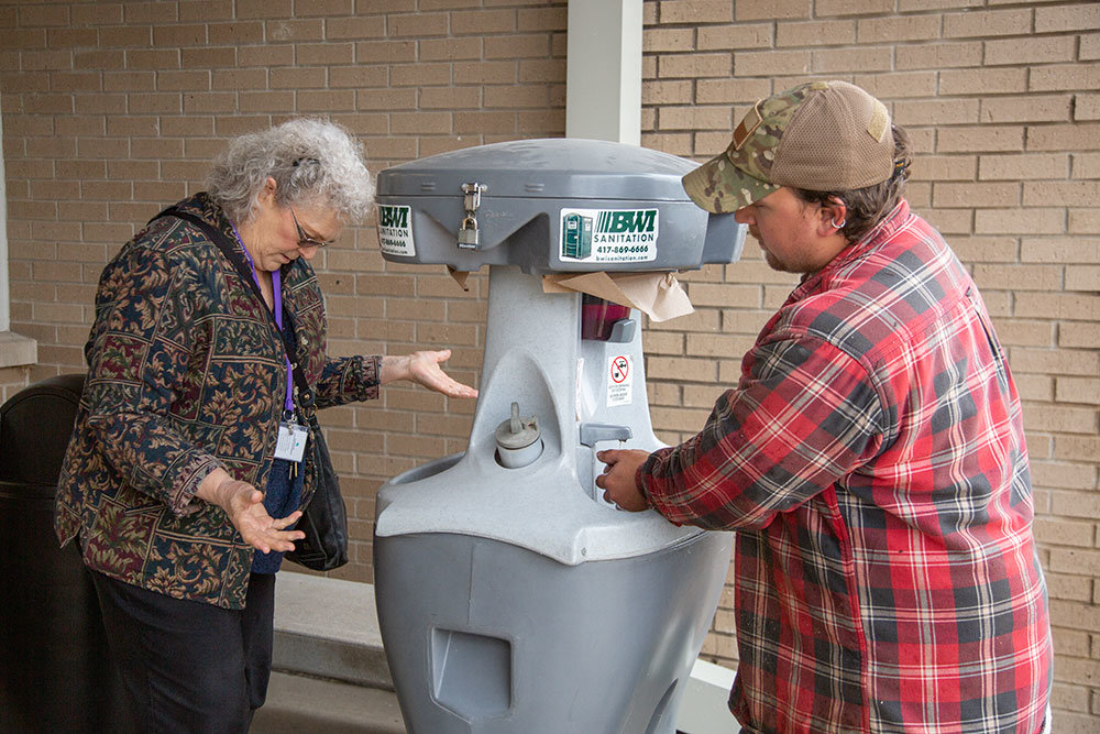 STAY CLEAN: A hand-washing station outside the entrance of Burrell Behavioral Health is a sign of the times during the coronavirus outbreak. Alex Schweidel, at right, of Carson's Nurseries and Dr. Penelope McAlmond-Ross sanitize their hands before entering the building March 17.