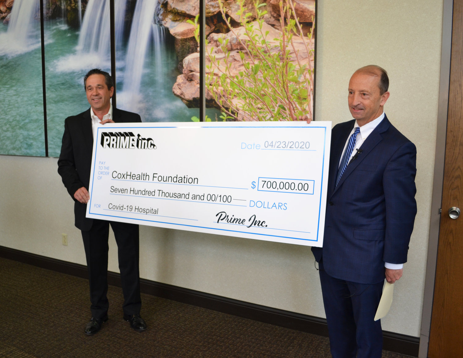 Darrel Hopkins, director of leasing and controller at Prime, left, presents a check to CoxHealth President and CEO Steve Edwards.