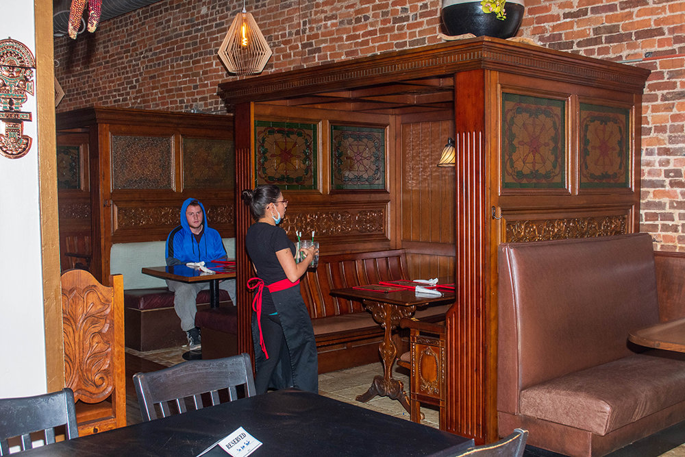 A server at Cafe Cusco prepares a table for guests on the restaurant's first night reopened.
