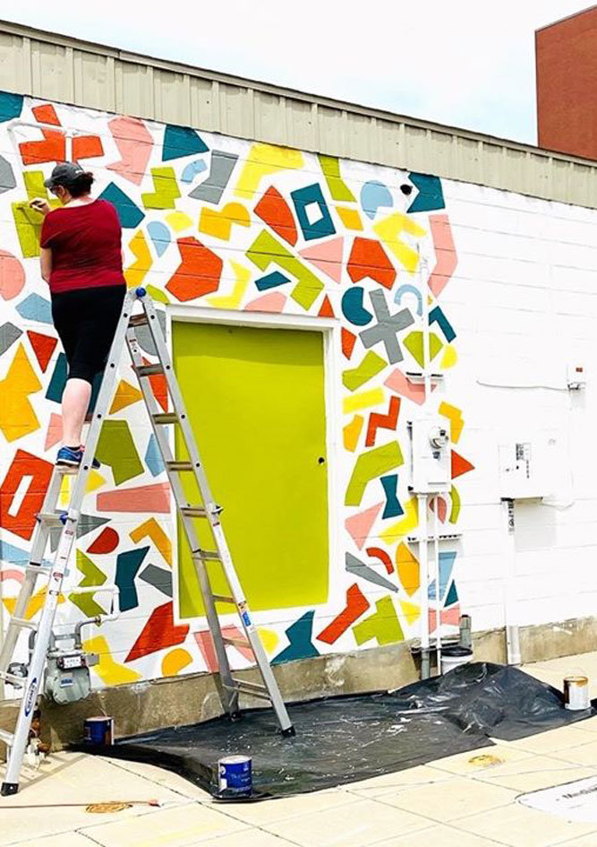 Christie Snelson of Obelisk Home works on a mural across from the store on West Phelps Street.