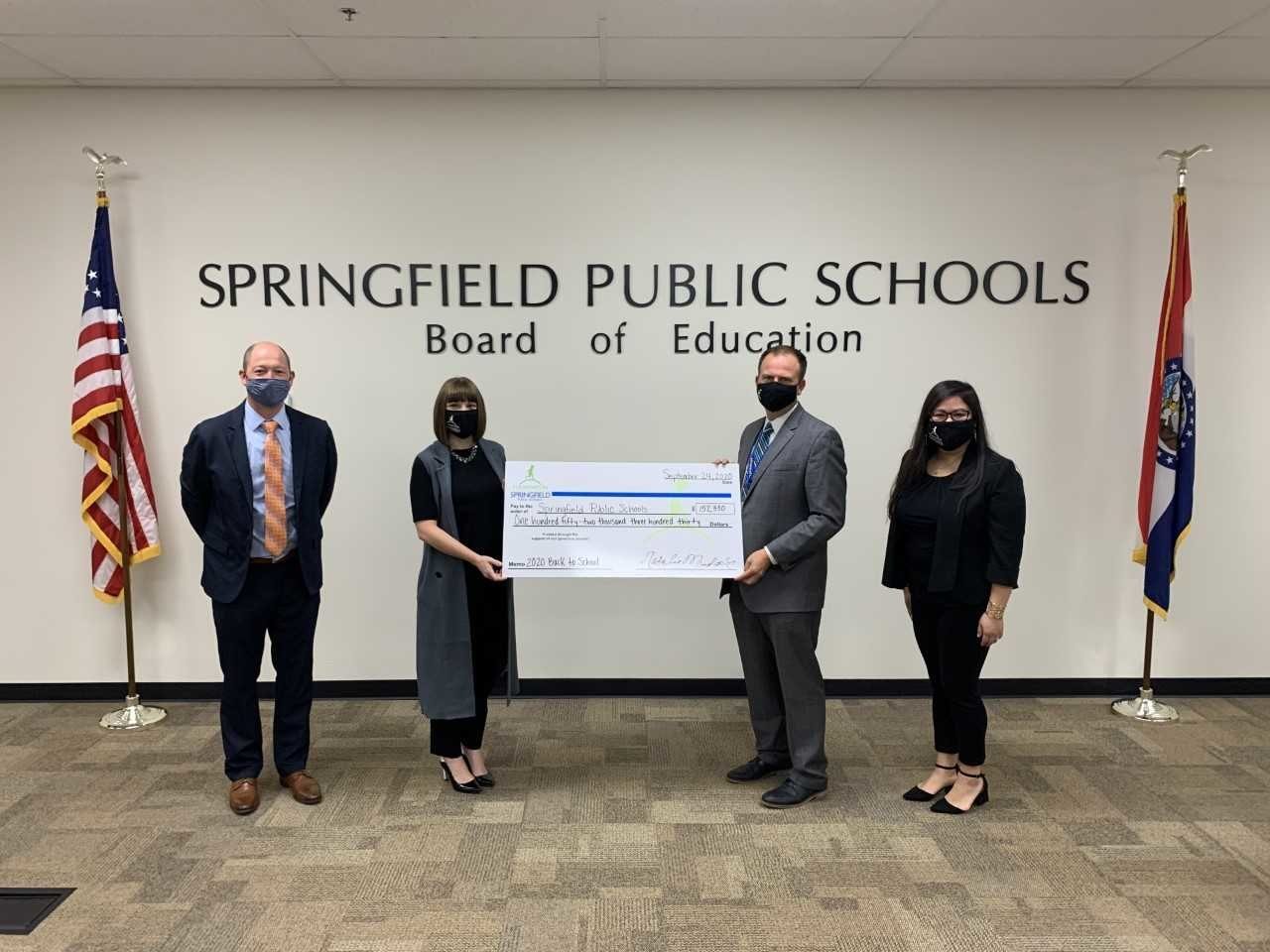 SPS Superintendent John Jungmann, second from right, accepts a ceremonial check from foundation officials, from left, Stephen Gintz, Natalie Murdock and Tina Pham.