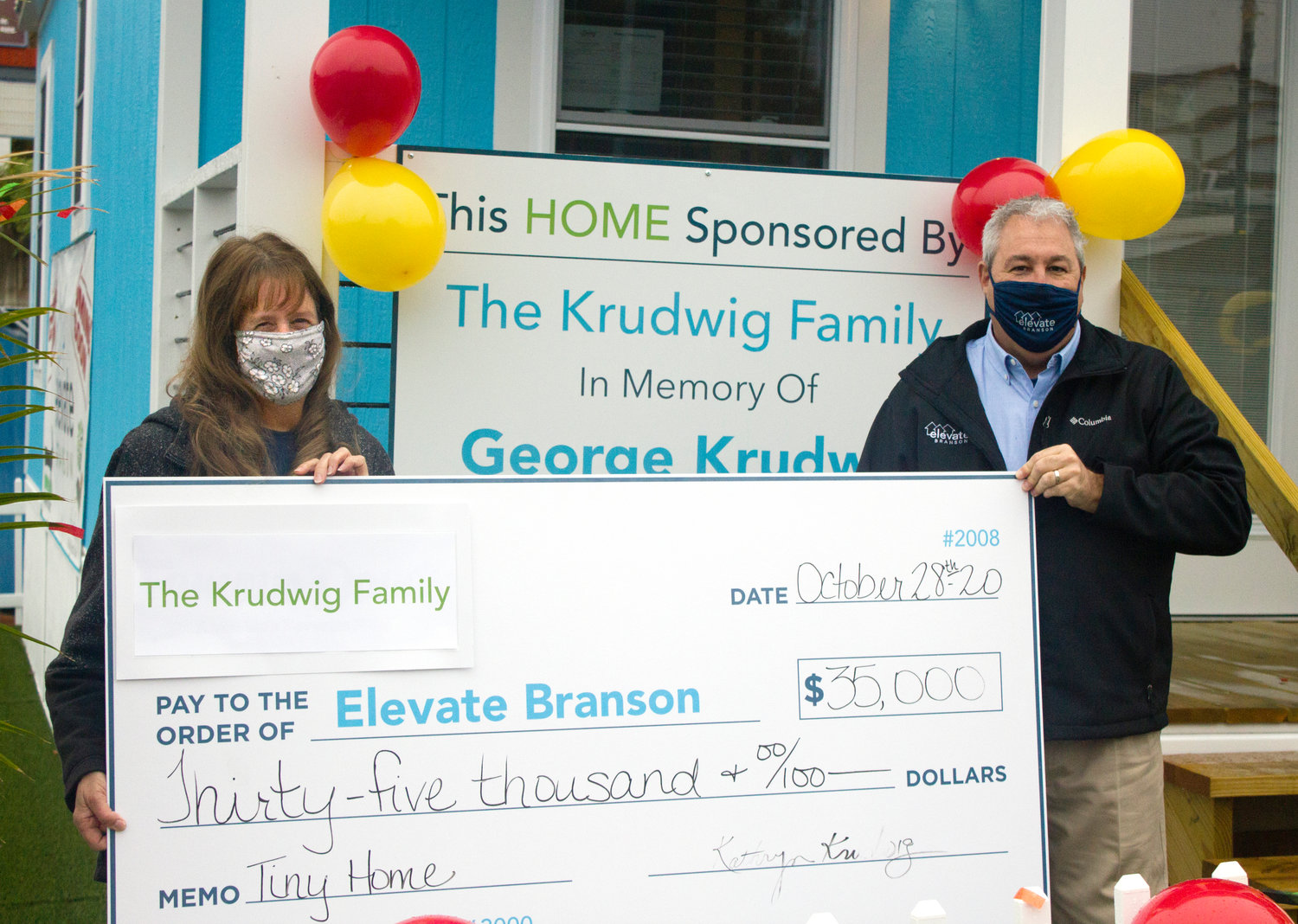 Kathy Krudwig presents a check to Elevate Branson founder Bryan Stallings.