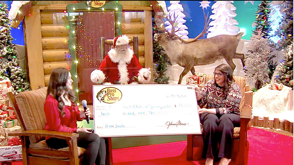 GOOD MORNING GIFTBoys & Girls Clubs of Springfield CEO Brandy Harris, right, receives a surprise $20,000 donation during the Springfield Area Chamber of Commerce's final Good Morning, Springfield event of the year. Sarah Hough, Bass Pro Shops community affairs manager, left, and a staffer dressed as Santa Claus presented the check during the Dec. 3 livestream.