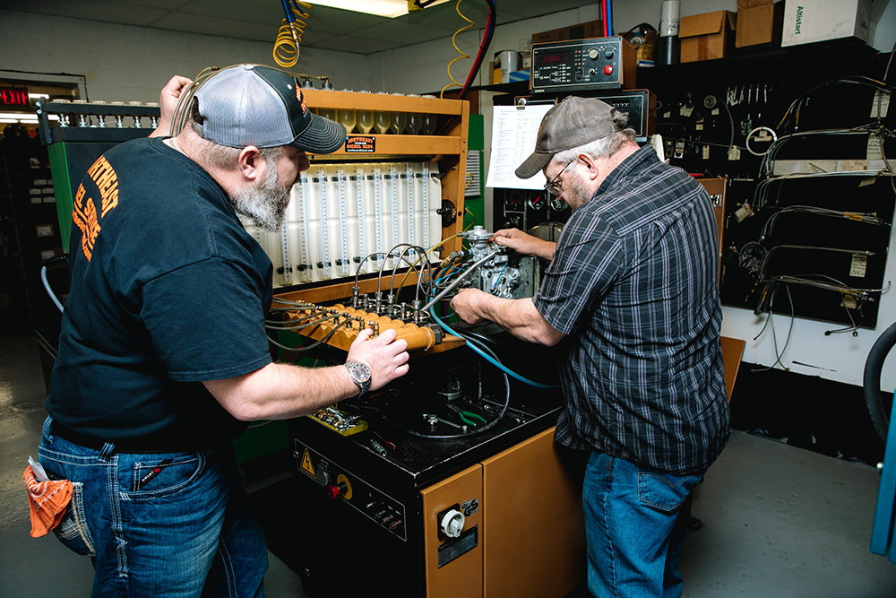 "ENGINE MAVENS: Northeast Diesel Service of Springfield Inc.'s Mike Glover, left, and Rick ""Cooter"" Perrigo make fuel injection repairs at the company's East Division Street shop."