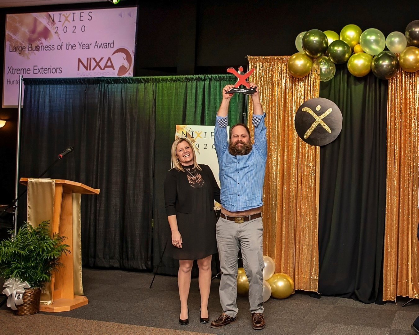 Summer and Hunter Lampe of Xtreme Exteriors celebrate their win last month for the chamber's Large Business of the Year.