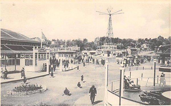 """A photo of the Monticello Amusement Park, showing the entrance to the dance hall (left) and the towering """"Aero-Plane"""" ride (center)."""
