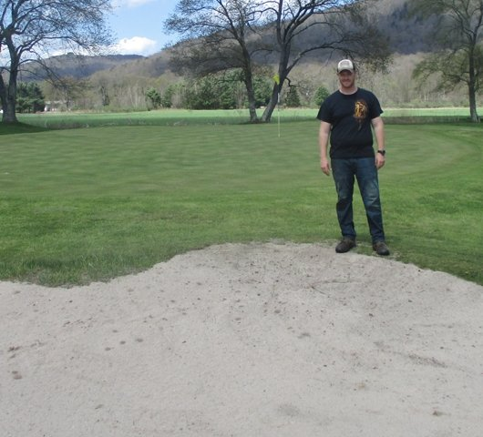 Twin Village Golf Course Superintendent Greg Feeney Jr. stands between one of the restored greens and restored and reshaped sand traps as the course officially opened last week.