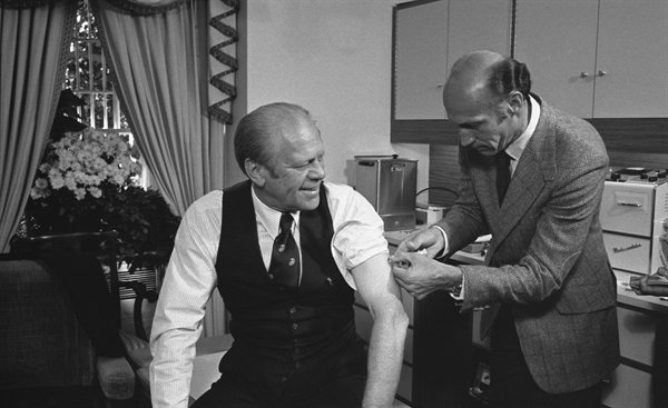 President Gerald Ford is photographed getting vaccinated against the swine flu in an effort to convince Americans to follow suit.