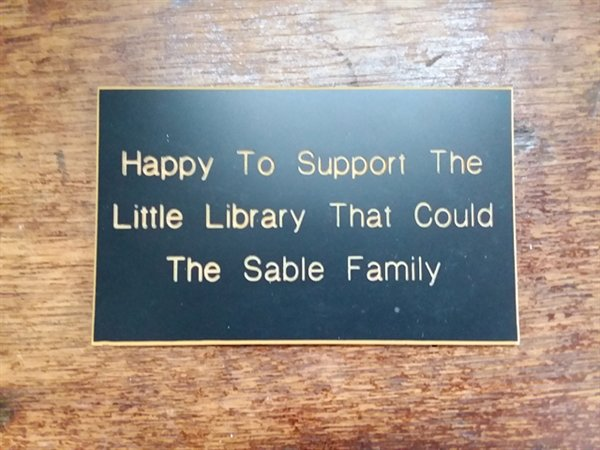 """Nancy Stevenson was a volunteer at the Sunshine Hall Free Library who handled media and publicity. As one of the oldest and smallest libraries in the RCLS, Nancy labeled the Library as the """"little library that could."""" Through a generous donation from the Sable family, in addition to the plaque (photo), her in memoriam legacy is now in the library's Nancy Stevenson Kids Corner in the Main Reading Room."""