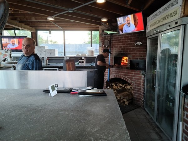 Local businessman and philanthropist, Lou Monteleone and his brother Frank, make the specialized thin crust pizzas in their wood burning oven at the popular Pizza Piazza in Eldred.