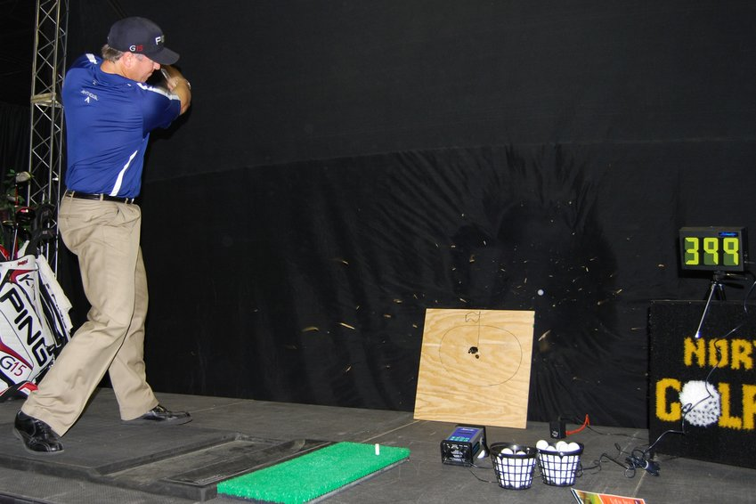 Long Driving Champion Brian Pavlet drives a golf ball through this one-half inch plywood board. The ball can be seen coming out of the back of the board as the wood splinters fly in the air.