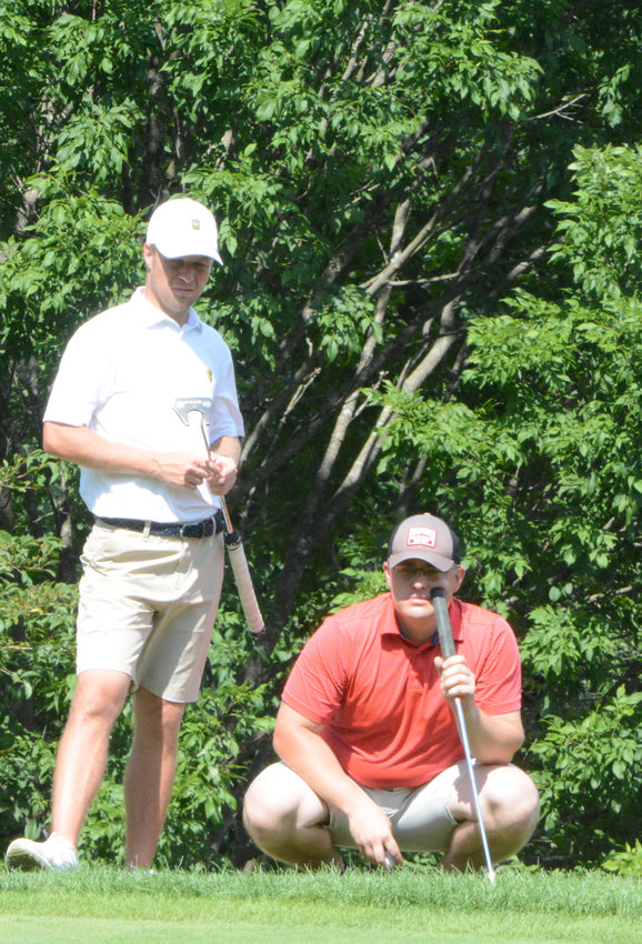 Joe Winski, kneeling, and partner Sean Semenetz look over a putt during last year's Championship match. The duo will be back to defend their title this year.