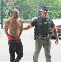 Deputy Sheriff Corey Dixon escorts Charles Ellis into the Sheriff's Office headquaters on Wednesday, August 11. It is alleged that Ellis intentionally started the fire at 428 Fraser Road on August 2.
