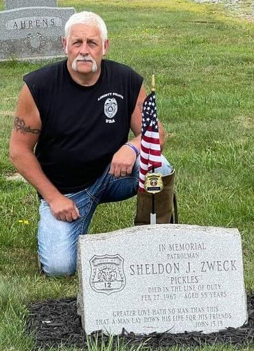 Keith Herbert kneels besides the Sheldon J. Zweck memorial at the Liberty Cemetery as part of the memorial motorcycle poker run August 14th.