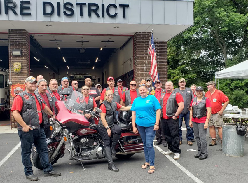 Kevin McCombs' wife Helen (light blue t-shirt) with members of the Red Knights, NY Chapter 39 outside of the Woodridge Firehouse on Sunday.