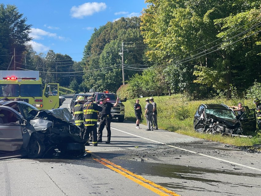Police and rescue workers talk with injured passengers and the driver in a Volkswagon as the car that hit them, a 2005 Chevrolet Trailblazer, lies disabled in the center of Route 17B, seen at left.