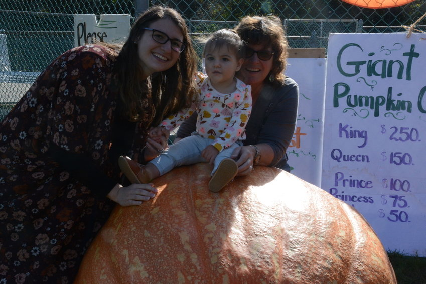One of the traditions of the event is the Giant Pumpkin Contest. Taking a closer look at this pumpkin is Ryleigh Herbert, who will soon celebrate her first birthday. She's pictured with her mother, Ashley (at left) and grandma Leah Exner.