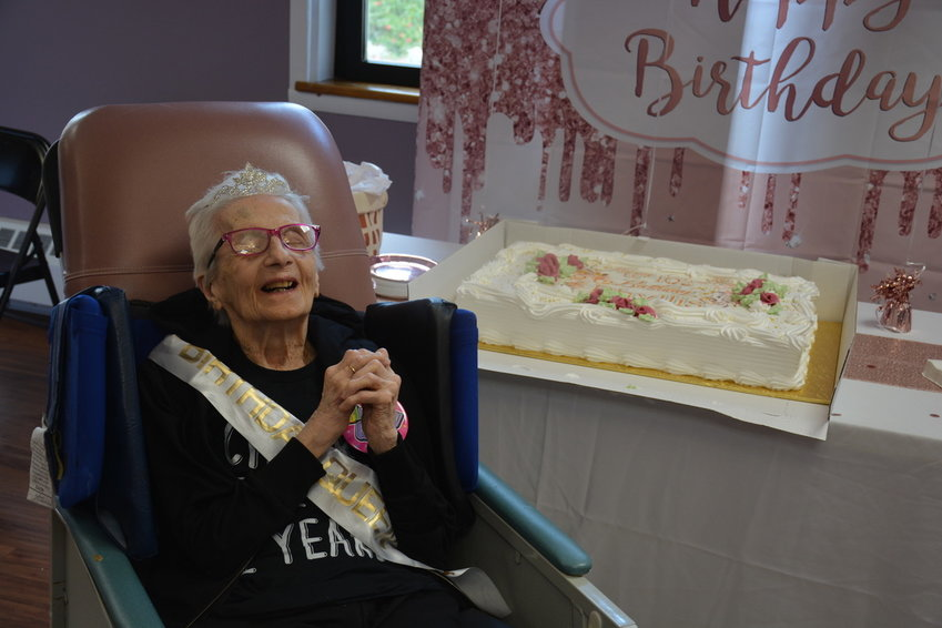 Phyllis Dougherty smiles as friends and Achieve staff sing her happy birthday prior to having some celebratory cake.