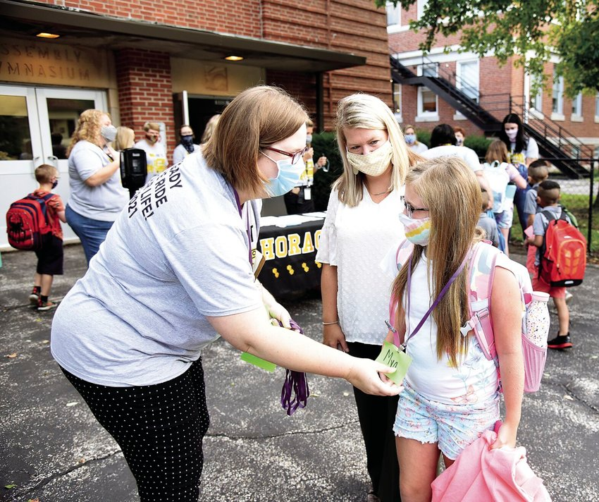 Tuesday morning, Horace Mann Elementary mixed-aged third and fourth grade teacher Ashley Wendt gives third-grader Mya Sheeley her name tag while her mother, Kara Sheeley, watches. Students and staff returned to school Tuesday with face masks and COVID-19 protocols for the upcoming school year.