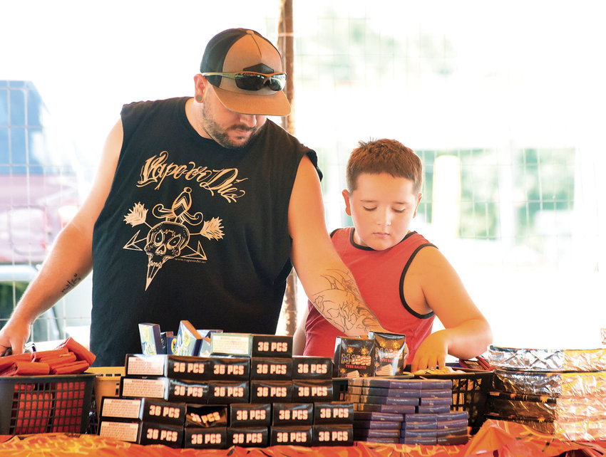 Cody Slaughter and his son Chase Slaughter, 10, of Sedalia, shop for fireworks Thursday afternoon at Hale Fireworks on South U.S. Highway 65. Slaughter said they were going to enjoy fireworks on July 4, but also had a big holiday weekend planned.