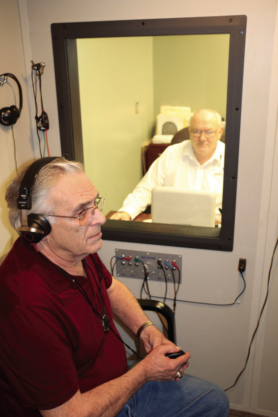Gerald Young, background, hearing instrument specialist with Bothwell ENT, administers a hearing test to Paul Sitzes.