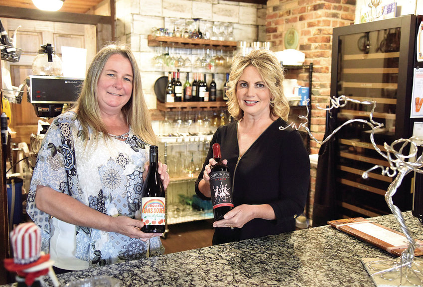 Wednesday afternoon, Judy Smasal, right, owner of Wine Women & Song in Cole Camp, and General Manager Andra Newson hold bottles of wine available at the gift shop and café which has been open for a little over a year.