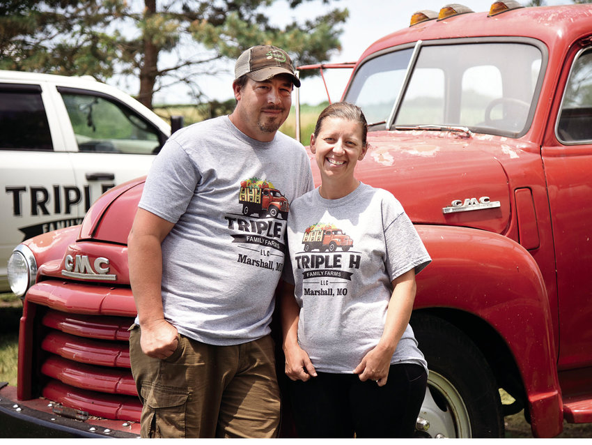 Wednesday afternoon, Matt and Kim Tennill, owners of Triple H Family Farms LLC, of Marshall, stand beside a red 1946 GMC truck that has become the farm's logo. The couple grows a wide variety of produce and is members of the Sedalia Area Farmers' Market.