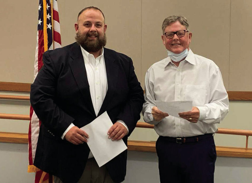 Justin Hubbs, left, is congratulated by State Fair Community College President Randy Eaton after taking the oath of office as a trustee Thursday afternoon in the Thompson Conference Center at SFCC. Hubbs was elected to the board in the June 2 municipal election.