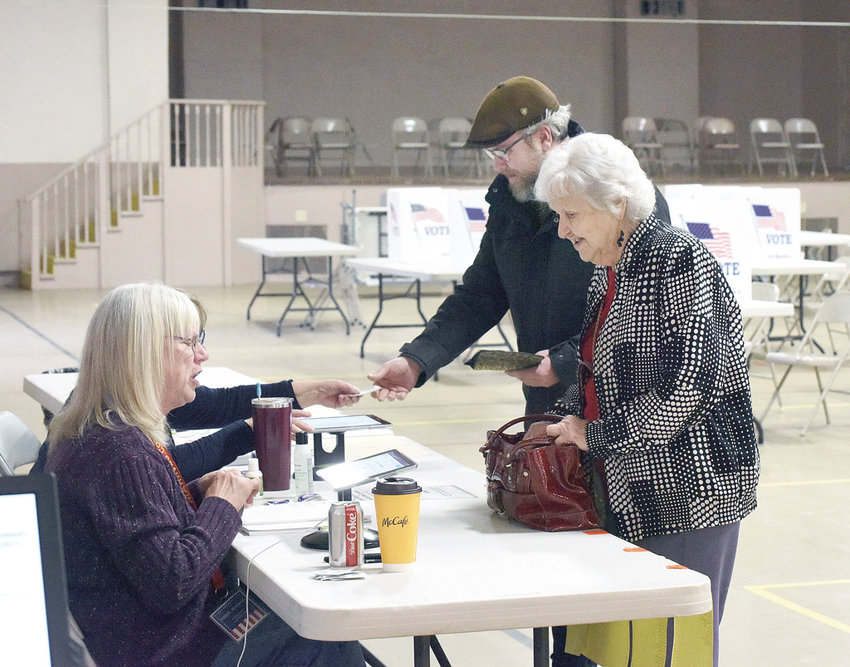 On Tuesday, Damon Freed and Donna Bartley prepare to show their ID to election judges in the Fist Ward at Convention Hall. At 11:08 a.m., 210 people had voted in the First Ward. Voter turnout in the Missouri Presidential Preference Primary was lower than predicted in the Sedalia area.