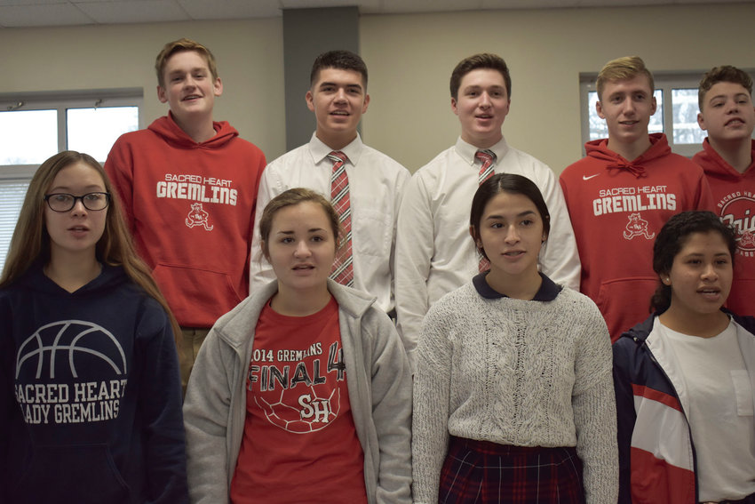 Sacred Heart Choir students practice Thursday morning for their performance that evening at State Fair Community College's Jingle on the Green. Pictured row one from left: Amelia Schott, Addison Trammell, Arly Ponce, Martha Angel. Row two: Dayton Martin, Kaleb Woolery, Jeff Hollobaugh, Lucas Martin, Donovan Dobson.