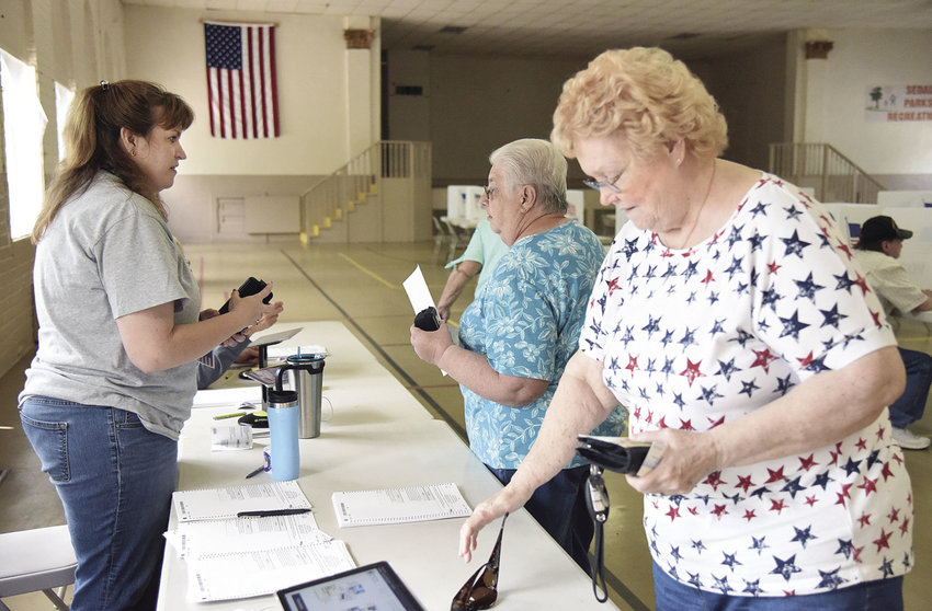As Election Judge Michelle Sparks looks on, Cheryl Keeting, center, and Dianne Roche, right, prepare to vote Tuesday afternoon at Convention Hall. As the women voted, a line of voters formed to cast their vote in the First Ward during the special election concerning the building of a new community center.