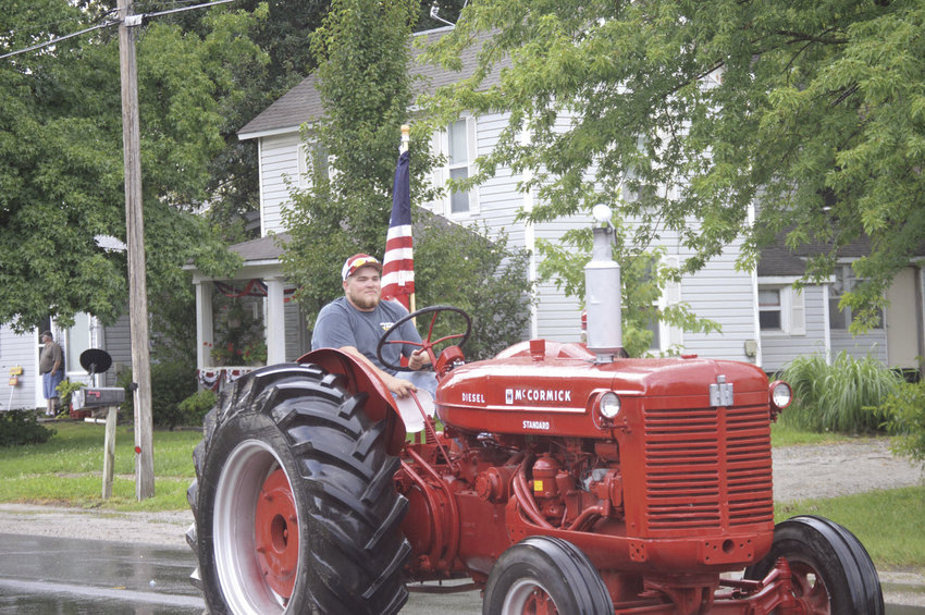 Joran Sawford proudly displays an American flag as he drives one of his McCormick tractors during the Smithton Town and Country Fair Parade in this Democrat file photo. The 52nd annual Smithton Town and Country Fair is scheduled for July 11 through 13.