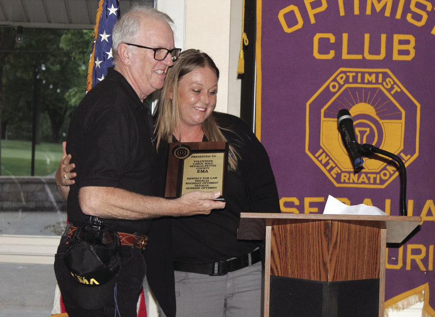 Sedalia-Pettis County Emergency Management Agency Director Trisha Rooda, right, gives a hug to Leonard Hall, who accepted the Volunteer of the Year award on behalf of his wife, Carol, who died unexpectedly earlier this year, at Thursday night's Optimist Club annual Respect for Law banquet at the Sedalia Country Club.