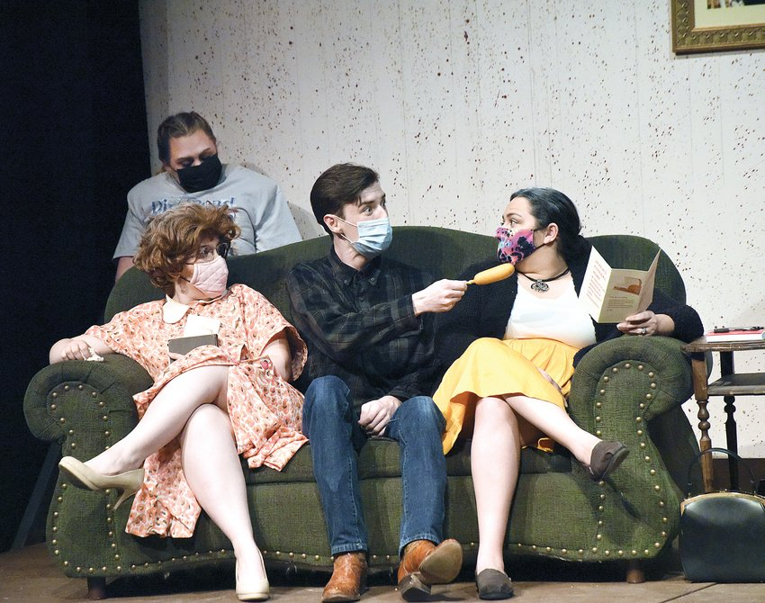 """Junior (Aren Goodwin) gestures with his corn dog as the Turpin family discusses casket options for their late relative, Bud, during a dress rehearsal Monday night for """"Dearly Departed."""" From left are Delightful (Brianna Harlow), Marguerite (Kennedy Keele), Junior and Raynelle (Sarah Hensel). State Fair Community College Theatre Arts students will perform the comedy Oct. 15-18."""
