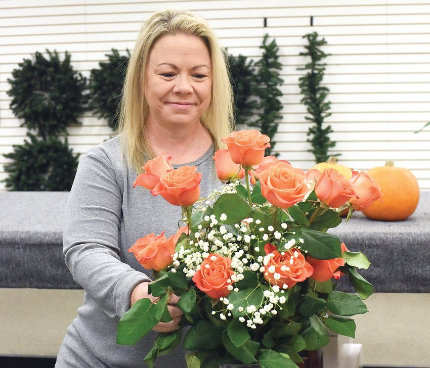 Stacy Riddle arranges flowers for a delivery Tuesday morning at the newly opened Flower and Vine Floral and Gifts in Thompson Hills Shopping Center. Riddle opened the family-operated shop, which offers a full line of flowers and gifts, Sept. 7.