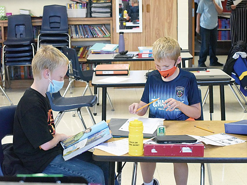 """Due to the COVID-19 pandemic, Charles """"Chase"""" Ueligger, right, and Marius Prior wear face masks while working on their assignments Thursday afternoon at Skyline Elementary School. Both boys are in Jessi Young's fourth grade class."""