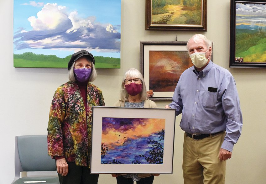 "Thursday morning, Sedalia Mayor John Kehde stands with Sedalia Visual Art Association Secretary/Treasurer Glenda Miller, left, and member Shirley Horacek, the Mayor's Choice Winner. Horacek received $100 as the winner for her collage, ""Dawning,"" in the new SVAA exhibit ""Missouri Skies"" showing in the Sedalia Municipal Building's foyer."
