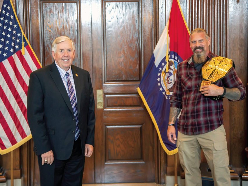 "Practicing social distancing, Missouri Gov. Mike Parson, left, greeted Kelly Murphy, University of Central Missouri director of Military and Veteran Services and first-ever winner of the CBS program ""Tough as Nails,"" during a visit to the Missouri state capitol Sept. 16."