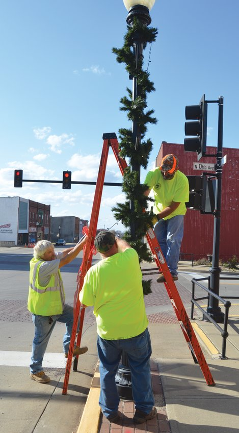 City workers attach new LED lights and garland to a lamppost in downtown Sedalia Monday, Nov. 9.