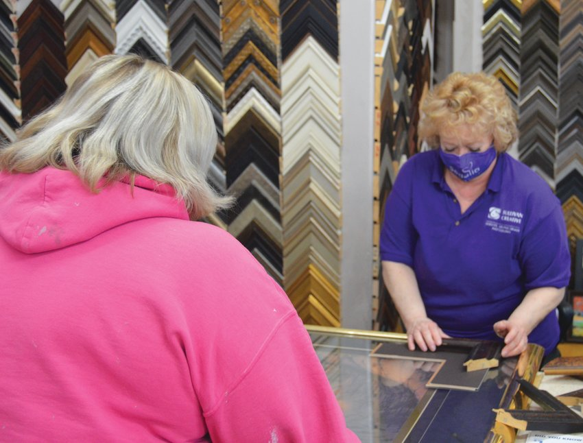 A shopper is helped with a frame for a picture at Art Impressions Gallery & Framing Friday afternoon in downtown Sedalia.