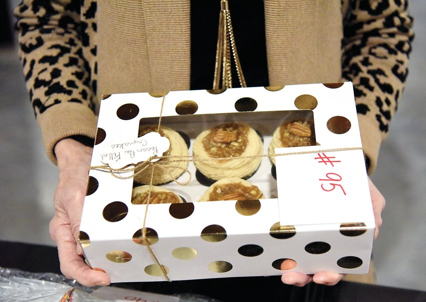 Dorothy Herndon, a development assistant with Child Safe of Central Missouri, holds a box of pecan pie-filled cupcakes Tuesday afternoon at the Child Safe Dessert Auction hosted at Foundry 324. Due to COVID-19, the annual Dessert Auction was hosted as a virtual event this year and featured cash-and-carry deserts and also desserts for auction.