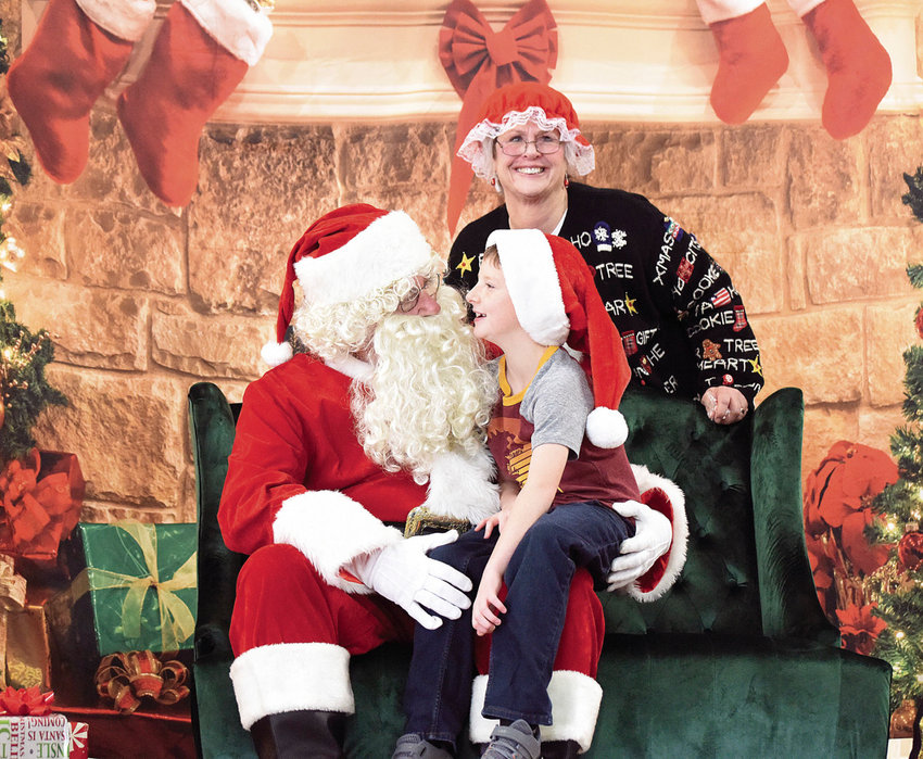 Matthew Hopper, 8, the son of John Hopper of Sedalia, smiles as he tells Santa what he'd like for Christmas Saturday, Dec. 7, 2019, at the Sedalia Parks and Recreation Department Breakfast with Santa event at Convention Hall.