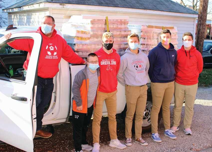 """Sacred Heart School collected its largest food donation in the history of the school's Thanksgiving food drive. """"Cases, not cans"""" was the challenge, and students in grades K-12 responded. SHS student leaders, faculty, and parents delivered 7,272 pounds of food to Open Door Ministries in November. That's 72% more than what was raised in 2019. All food stays local to support neighbors in need. Pictured: Chris Martin '93 hauls a truck full of food and helpers to Open Door. Pictured with him are his two sons, from left, Dylan and Lucas, and Lucas' fellow senior classmates, John Ulbrich, Dallin Chappell, and Jeffrey Hollabaugh."""