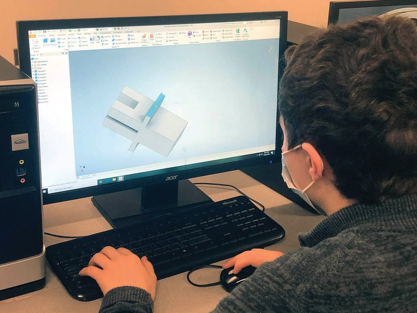 Smith-Cotton High School engineering student Arthur Gudoshnikov uses Autodesk Inventor to design a device to hold plexiglass on the side of a circular lunch table.
