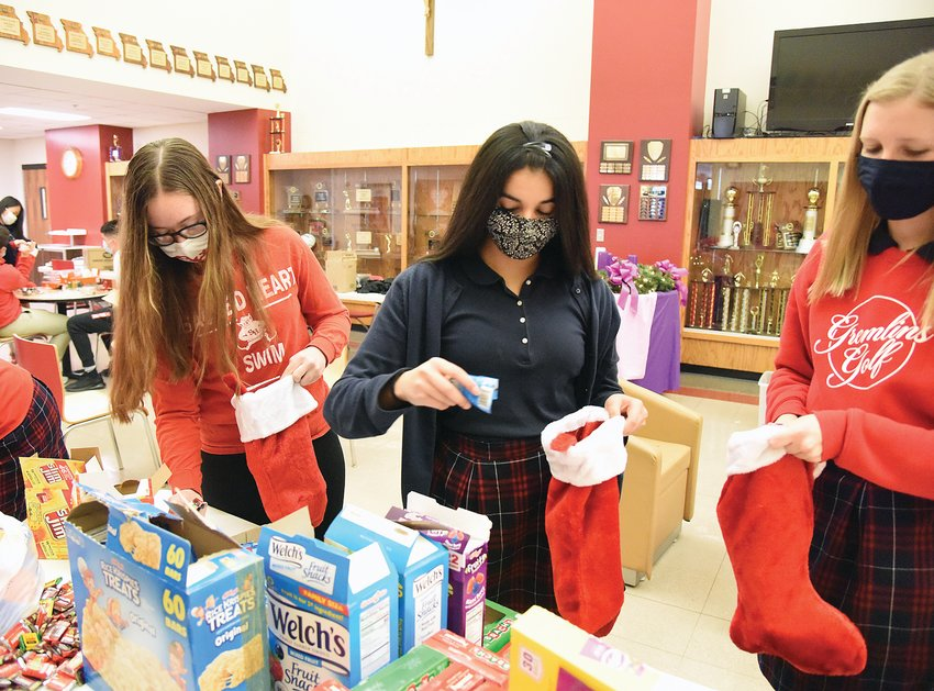 Friday afternoon, Amelia Schott, left, president of the Sacred Heart Key Club Chapter, and members Tania Bhardwaj, center, and Megan Wingerter place treats into stockings for Whiteman Air Force Base 509th Military Police Division. The club is giving the stockings to military members who can't go home for Christmas.