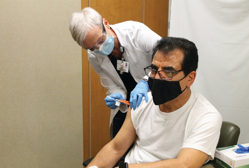 Sarah Wuellner, RN, of the Infection Control Department at Bothwell Regional Health Center, gives Dr. Assad Shaffiey, of Bothwell TLC Pediatrics, one of the first COVID-19 vaccines in Sedalia on Friday, Dec. 18, 2020.