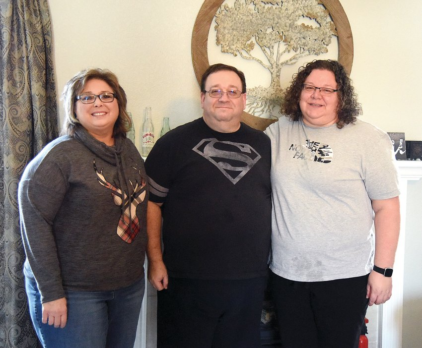 Brad Burch stands with his wife, Wendi, right, and their neighbor Delilah Nichols on Tuesday at the Burch home. In December, Brad's COVID-19 diagnosis led to the discovery of stage four melanoma.