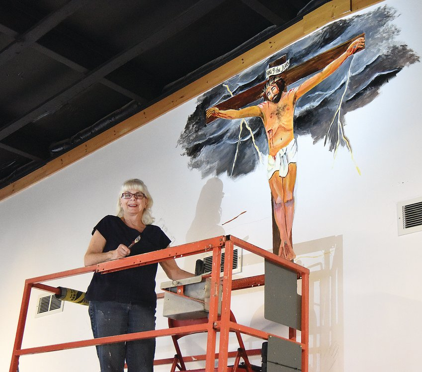 Tuesday morning, Artist Linda Hoover poses beside a large mural she's painting at Randall's Auto Collision and Service Center in Sedalia. The 16-foot tall mural depicts the crucifixion and resurrection of Jesus. Owner Adam Hall said he hopes the painting will be a conversation starter.