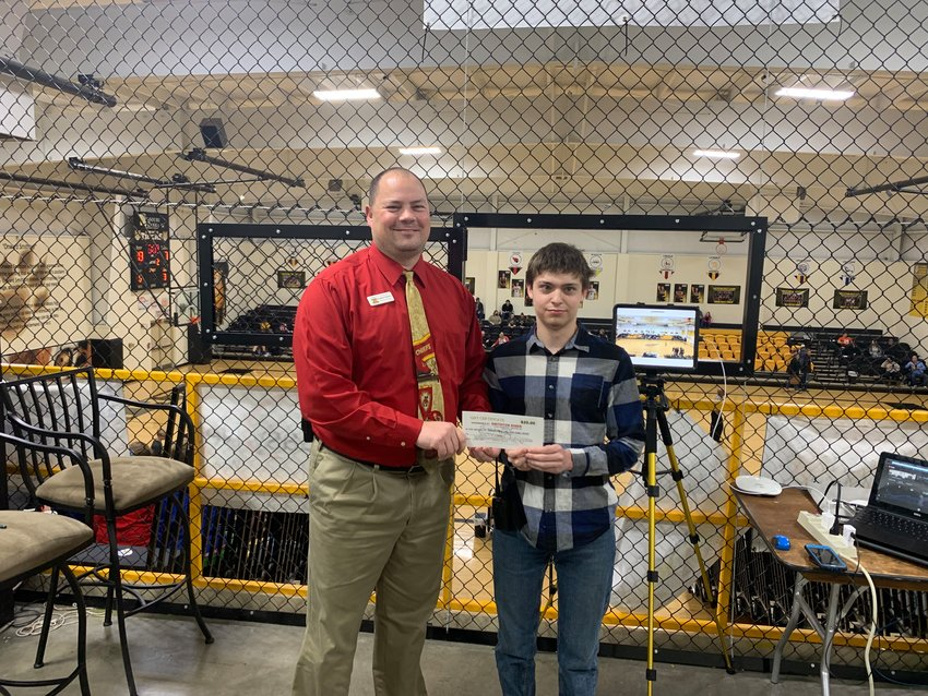 Principal Jonathan Petersen presents Smithton High School junior Jarett Davis with a $20 gift card to the Smithton Diner at a recent Smithton basketball game. Behind them is Davis' equipment for recording and live-streaming sports games.